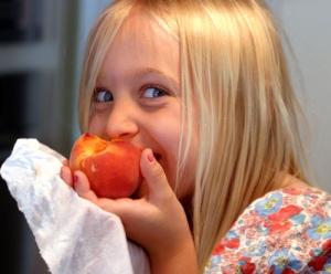 girl eating a peach